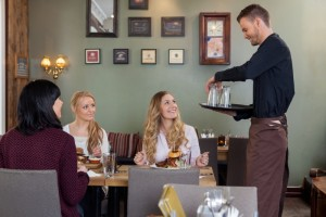 5156890-waiter-with-tray-of-glasses-while-female-customers-having-meal (1)
