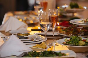 Relatively long table at low angle, dishes and wineglasses served for an upcoming banquet event. Salad, soup, casserole, variety of wine. Triangularly folded napkins. Blur behind focal point.